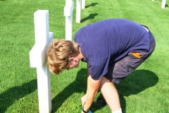 Meuse-Argonne American Military Cemetery:  A young RDVF tour adorns the grave site of one fallen Rainbow Division soldier with a commemorative flag.