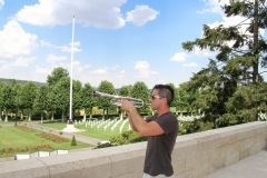 """Aisne-Marne American Military Cemetery:  Robert Contini, formerly of the 42nd Infantry Division Band, performs """"Taps"""" for those lost in action during the Second Battle of the Marne, summer 1918."""